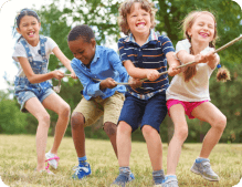 group of children are pulling the rope while smiling