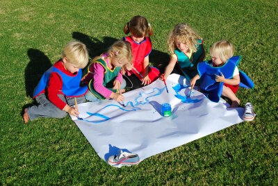 group of children are doing an art work while sitting at the playground